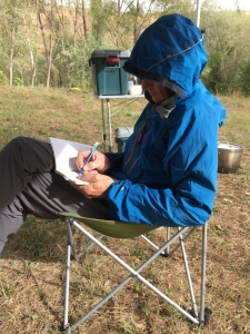 Michael trying to stay warm and dry while writing his route notes