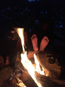 Michael warms his feet by the fire